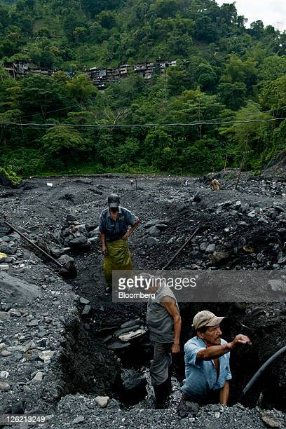 Emerald hunters known as guaqueros sift through mud and rocks searching for stones that have been washed downstream from the mines in Muzo Colombia...