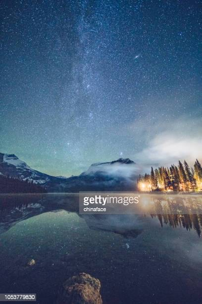 emerald lake with illuminated cottage under milky way - canada imagens e fotografias de stock