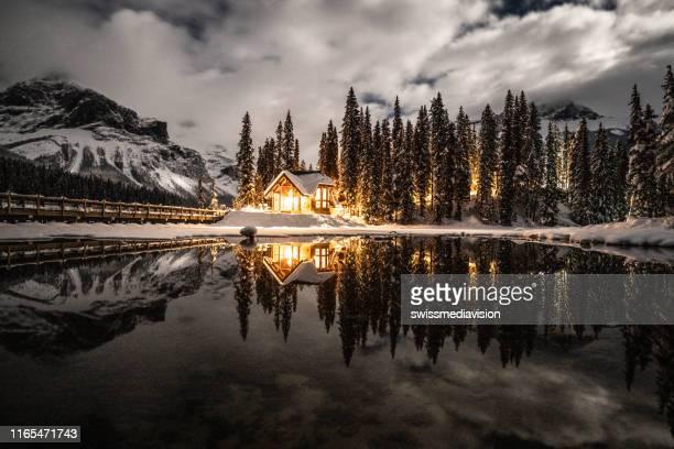 lac d'émeraude avec pavillon dans le parc national yoho, colombie-britannique, canada; tourné la nuit avec des lumières allumées dans la réflexion chalet sur le lac - chalet de montagne photos et images de collection
