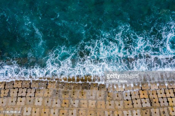 emerald waves washing off the seawall constructed of small cubical concrete structures - seawall stock pictures, royalty-free photos & images