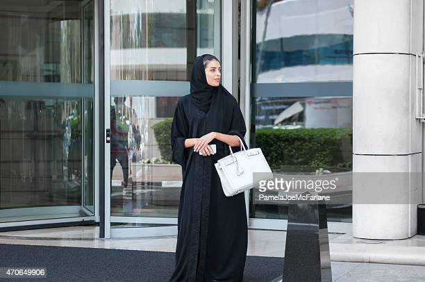 Emerati Woman in Traditional Dress with Cellphone Outside Modern Hotel