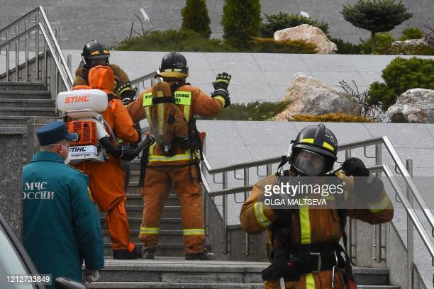 Emergencies personnel wearing protective gear spray disinfectant on colleagues at the site of a fire at the Saint George hospital in Saint Petersburg...