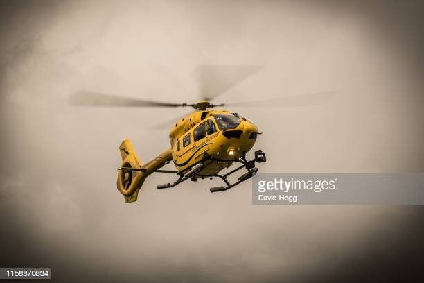 emergency ambulance helicopter landing on arran - helicopter rotors stock photos and pictures