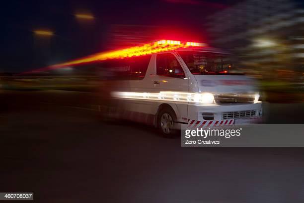 emergency ambulance speeding through city at night - red light stockfoto's en -beelden