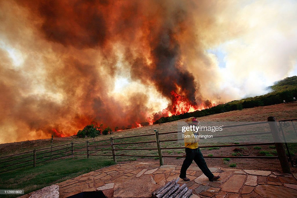 Emergency crews battle a running wildfire that is threatning a home on April 19, 2011 in Strawn, Texas. Dozens of area homes have been destroyed in the wildfires that have been fueled by dry conditions, high winds, and low humidity.