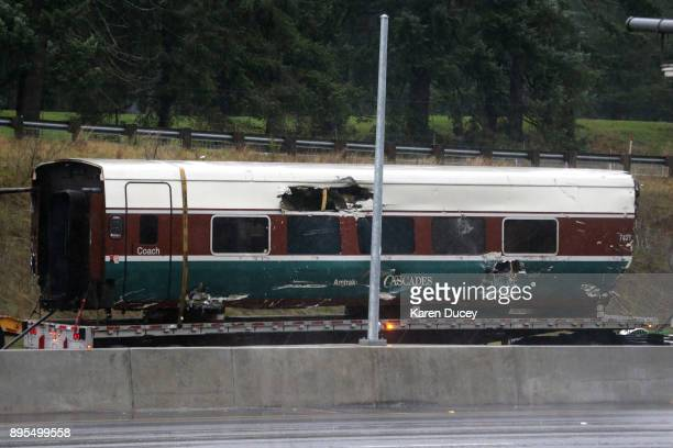 Emergency crews continue lift a train car off the bridge after an Amtrak train that derailed onto Interstate 5 the previous day killing several...