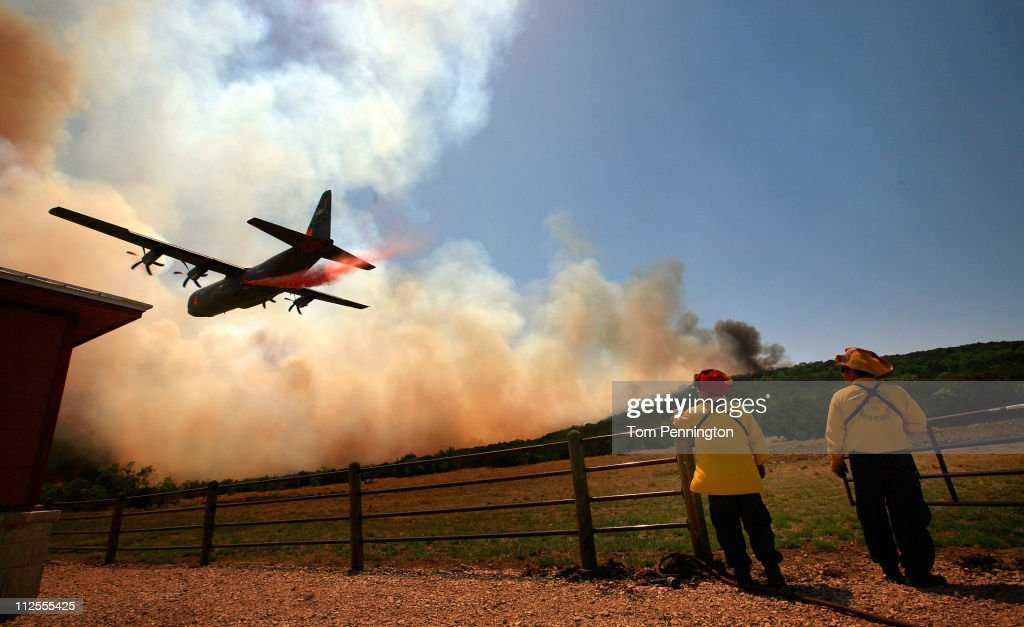 Emergency crews drop a fire retardant slurry on a running wildfire to save a house on April 19, 2011 in Strawn, Texas. Dozens of area homes have been destroyed in the wildfires that have been fueled by dry conditions, high winds, and low humidity.