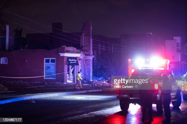 Emergency crews work near a damaged business at Jefferson St and Seventh Ave N on March 3 2020 in Nashville Tennessee A tornado passed through...
