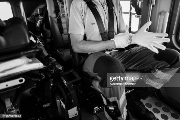 Emergency doctor Martin Fleiderer, crew member of the DRF Luftrettung emergency air medical services prepares gloves with a patient at Charite...