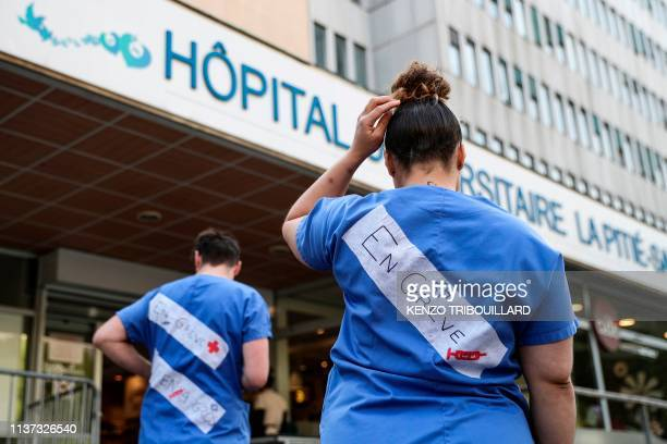 Emergency employees of French public hospital system APHP wear messages reading on strike as they protest against working conditions at the entrance...