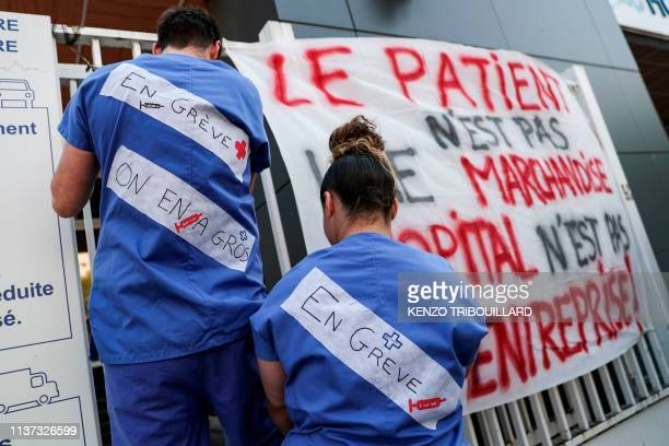 """Emergency employees of French public hospital system AP-HP wearing messages reading """"on strike"""" display a banner reading """"The patient is not a..."""