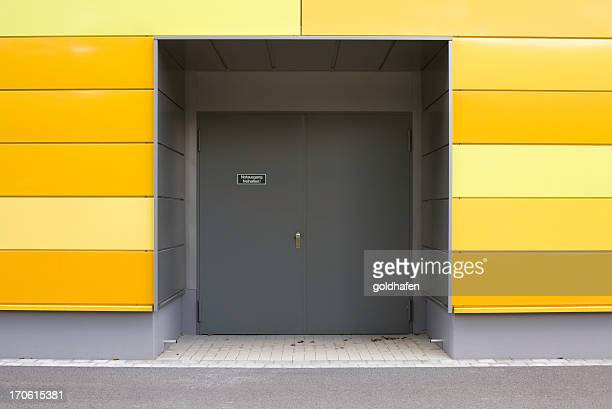 emergency exit and modern wall with yellow panels - industrial door stock pictures, royalty-free photos & images