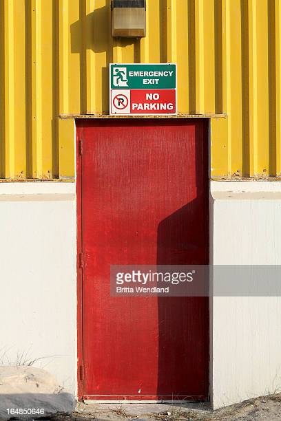 Emergency Exit' and 'No Parking' signs above door