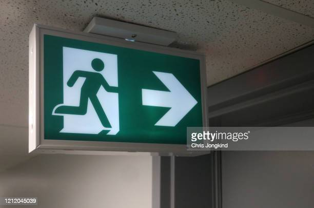 emergency exit sign pointing to door - evacuation stock pictures, royalty-free photos & images