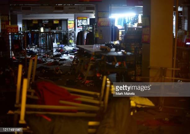 Emergency lights illuminate scattered merchandise strewn across the floor of a looted Modell's sporting goods store in the upscale Rittenhouse...