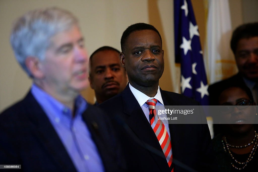 Emergency Manager Kevyn Orr (3R) listens to Michigan Governor Rick Snyder (L) speak during a news conference November 7, 2014 in Detroit, Michigan. Today U.S. Bankruptcy Judge Steven Rhodes gave the City of Detroit the okay to plan an exit strategy from Chapter 9 Bankruptcy.