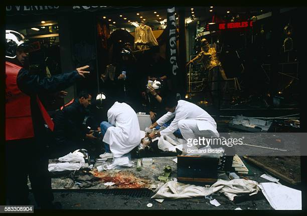 Emergency medical officers work desperately to treat a victim of a bomb explosion at the Tati department store on Rue de Rennes amongst the clothes...