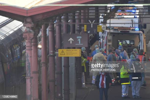 Emergency medical personnel carry a patient on a gurney into a medicalised TGV in Strasbourg station, eastern France, on March 26, 2020 as 20...