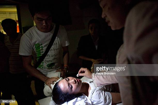 Emergency medical personnel work on a woman who fainted from shock at the Dusit Thani hotel after an attack by red shirts as the violence in central...