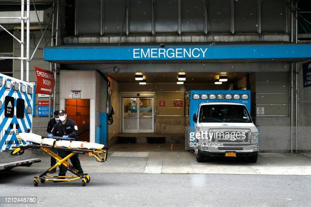 Emergency Medical Technicians move a gurney out of the emergency entrance into an ambulance at Mt. Sinai-Beth Israel Hospital amid coronavirus...