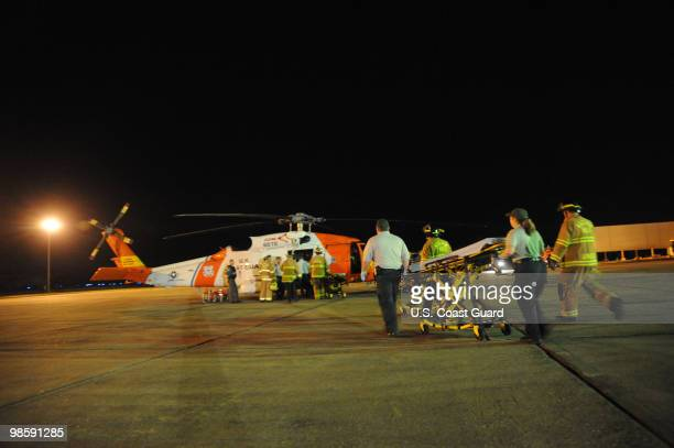 Emergency medical technicians rush a gurney to an awaiting HH60 rescue helicopter and crew from Coast Guard Aviation Training Center Mobile Ala at...