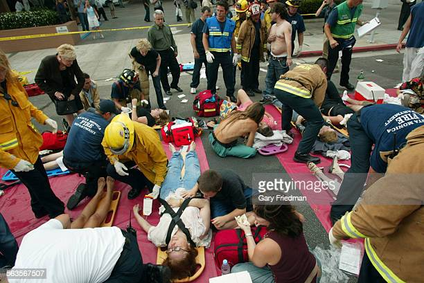 Emergency officials treat injured peoople in a triage area after a car plowed through a crowded farmers market in Santa Monica Calif Wednesday July...