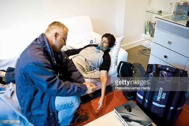 emergency on-call doctor administering oxygen to patient in home - dokterstas stockfoto's en -beelden