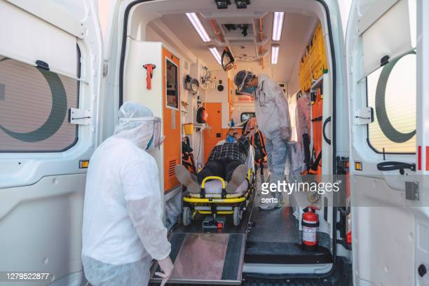 emergency paramedic staff with hazmat suit by male patient on stretcher in ambulance during pandemic - illness prevention stock pictures, royalty-free photos & images