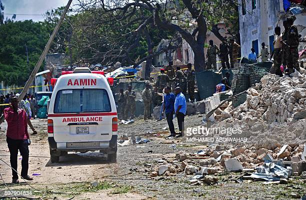 Emergency personnel and soldiers gather at the scene of a suicide car bomb blast on August 30 2016 in Mogadishu At least seven people were killed on...