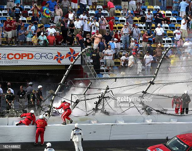 Emergency personnel climb the safety wall to get the burning wreckage that destroyed that catchfence at the finish line in the final seconds of the...