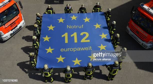 Emergency personnel from the Fire Station 1 holding up a flag with the inscription 'Notruf 112 europaweit' in Stuttgart Germany 18 July 2016 On 29...