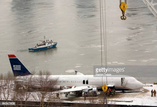 Emergency personnel inspect the US Airways Airbus A320 after it was lifted out of the Hudson River January 18 2009 in New York City US Airways Flight...