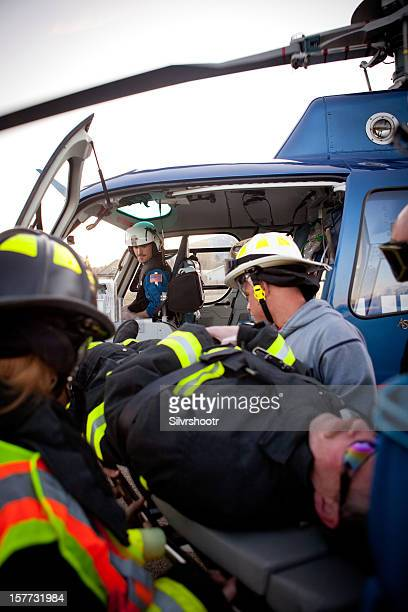emergency personnel loading patient into a helicopter - medevac stock photos and pictures
