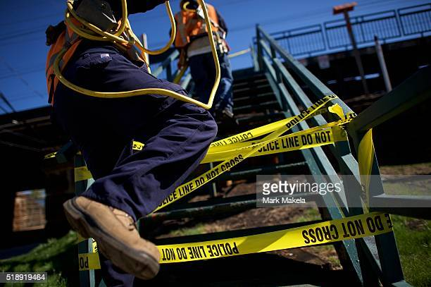 Emergency personnel pass equipment across police tape to work on train tracks near the crash site of Amtrak Palmetto train 89 on April 3 2016 in...