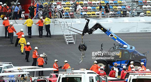 Emergency personnel remove a tire with front suspension from the front grandstand at Daytona International Speedway following a wreck on the final...