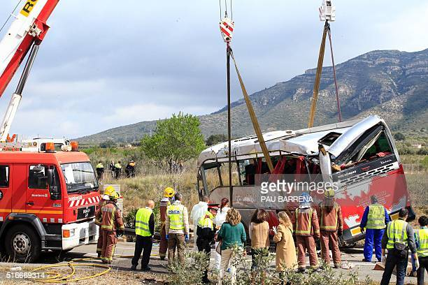 Emergency personnel stand as a crane rights a bus on the Spanish AP7 motorway near Freginals Amposta south of Tarragona following a fatal accident...