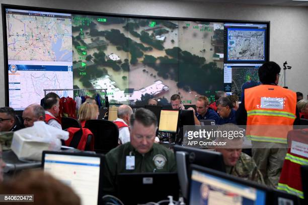 Emergency personnel work in the Texas Department of Public Safety Emergency Operations center in Austin Texas on August 29 as rains from Hurricane...