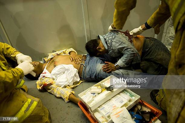 Emergency rescue squad medics from the Los Angeles Fire Department treat three South Asian men stabbed outside a convenience store on August 5 2006...