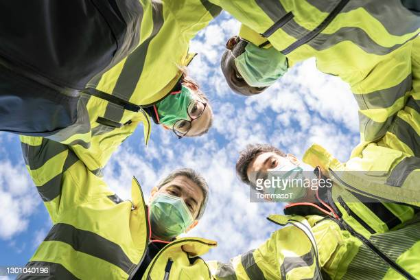 emergency rescue squad teamworking huddling together - rescue worker stock pictures, royalty-free photos & images