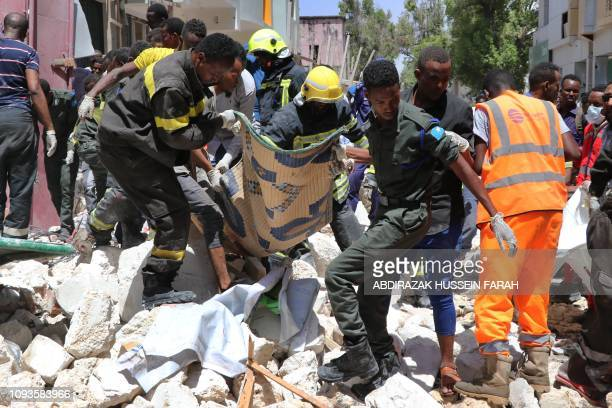 TOPSHOT Emergency rescue staff carry the body of a victim over rubble at the scene of a carbomb attack on February 4 2019 in Somalia capital...