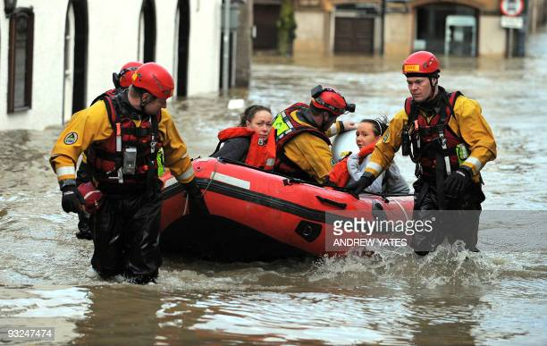 Emergency rescue workers use an inflatable boat to rescue flood stranded residents of Cockermouth, in Cumbria, north-west England, on November 20,...