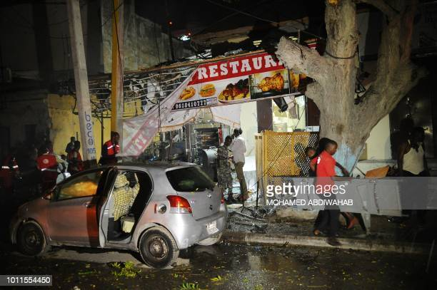 Emergency responders and security personnel work at the site of a car bomb explosion in Mogadishu on August5 2018 At least three were killed and...
