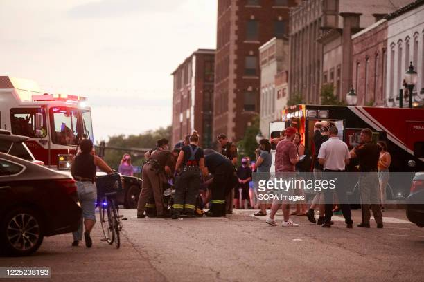 Emergency responders attend to a woman who was injured after a red car carried her and another protester several blocks at a high rate of speed...
