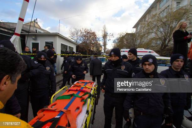 Emergency responders cross a police line to take a stretcher to the scene of the suicide bombing at entrance of U.S. Embassy in Ankara.