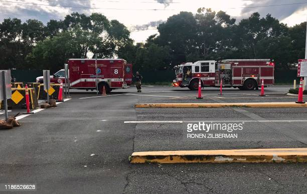 Emergency response vehicles wait outside the Nimitz Gate entrance to the Pearl Harbor Naval Shipyard to assist with a fatal shooting incident in...