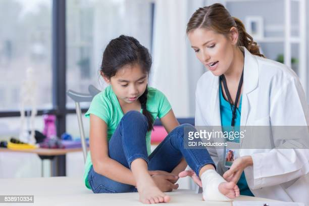 emergency room doctor explains young girl's injury - orthopedics stock pictures, royalty-free photos & images