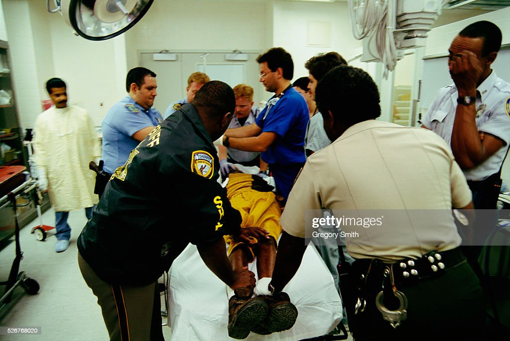 Physicians and Policemen Holding a Patient Pictures | Getty Images