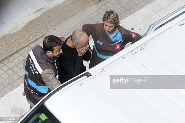 Emergency Service members accompany a man at the Joan Fuster Institue in Barcelona on April 20 2015 after a student allegedley broke into the school...