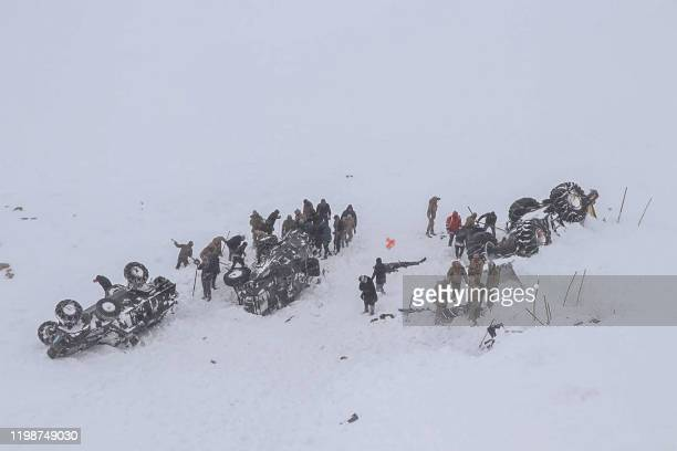Emergency service members dig in the snow around at least three overturned vehicles, near the town of Bahcesehir, in the eastern Turkey province of...