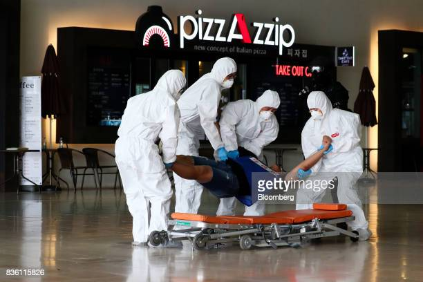 Emergency service personnel carry a man playing the role of an attacker onto a stretcher during a simulated chemical terrorism crisis as part of an...